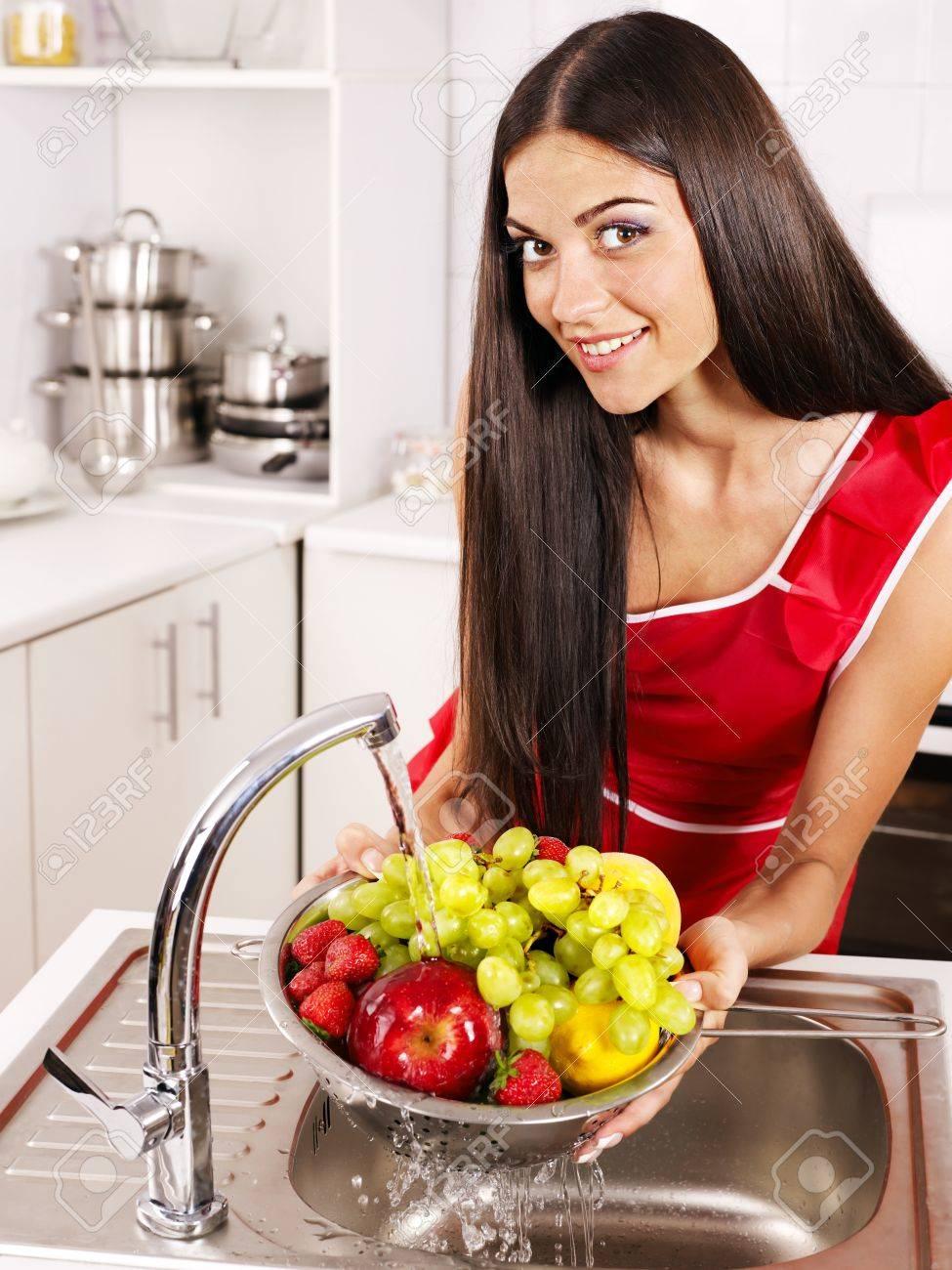 Happy woman washing fruit at kitchen. Stock Photo - 21173863