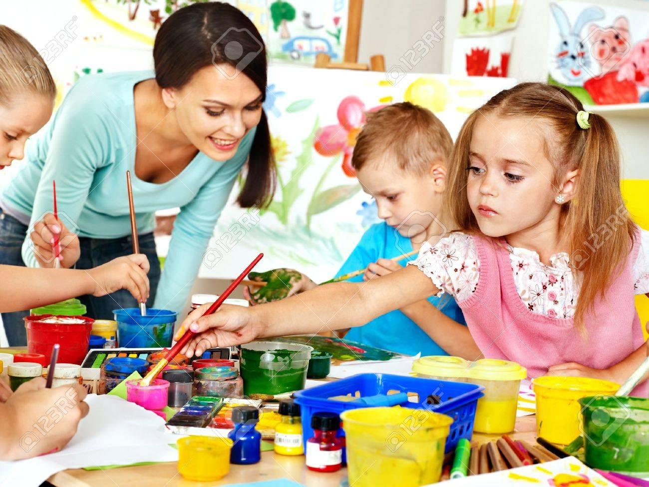 Happy children with teacher painting. - 21734044