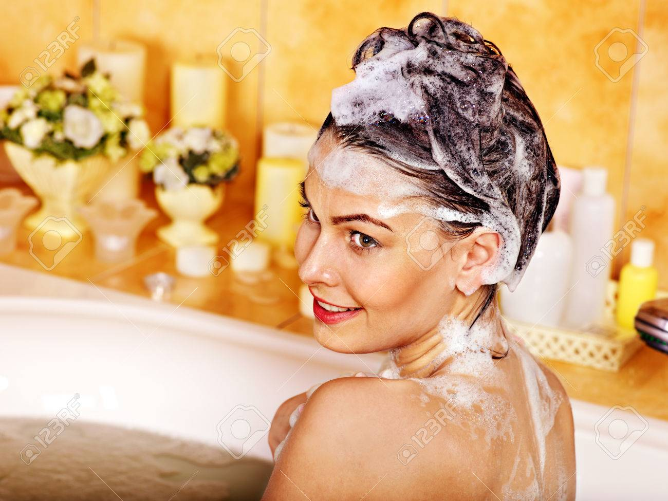 Woman washing hair in bubble bath. - 22673276