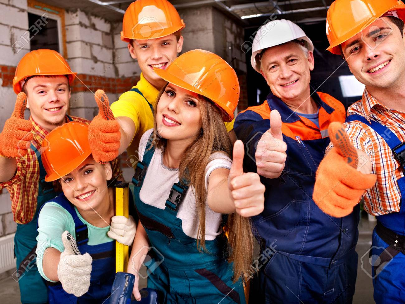 Happy group people in builder uniform thumb up. - 23856312