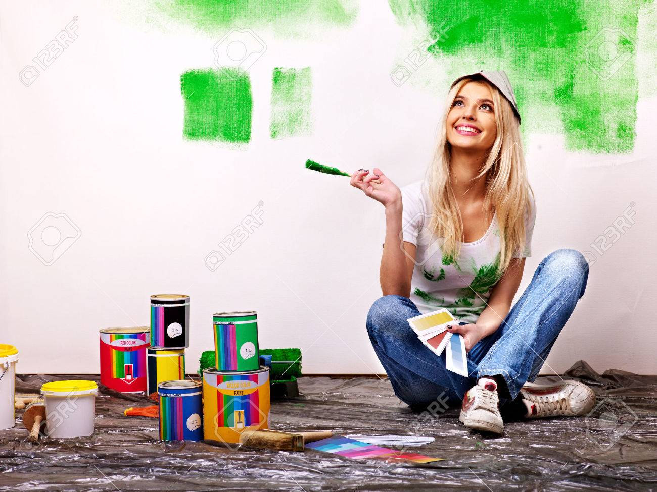 Happy woman paint wall at home. - 23856427
