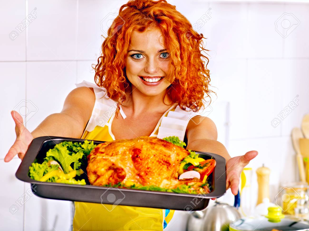 Young woman cooking chicken at kitchen. - 25073898