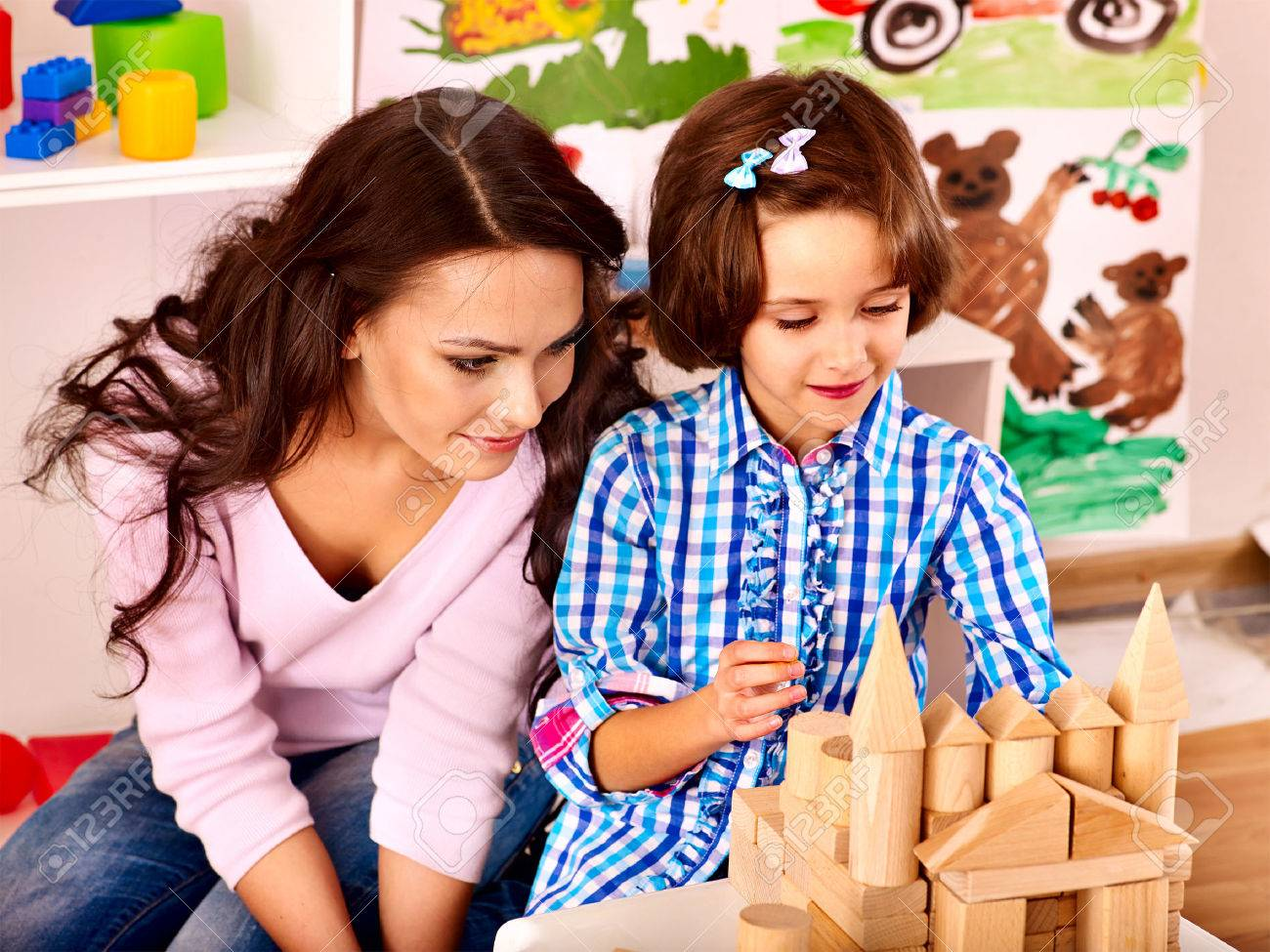 Family with children playing bricks. - 25225960