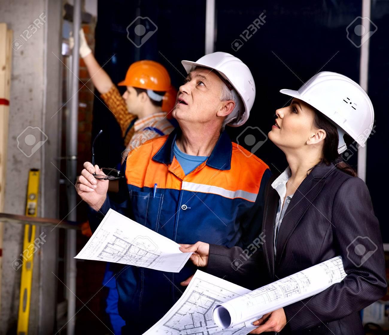 Business woman in builder helmet indoor. - 25226314