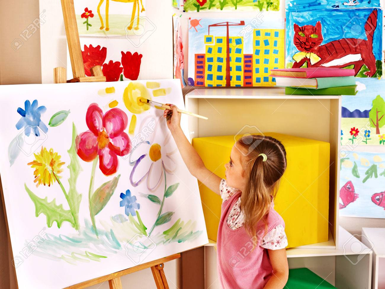 Child painting at easel in art class - 25499215