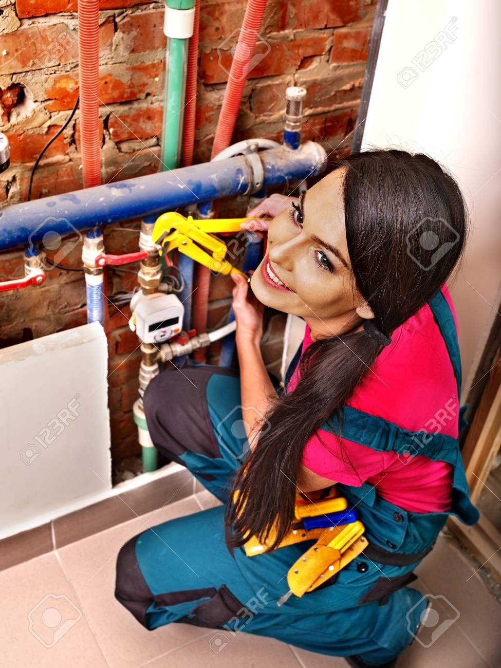Woman  builder fixing heating system with special tool. Stock Photo - 27461872