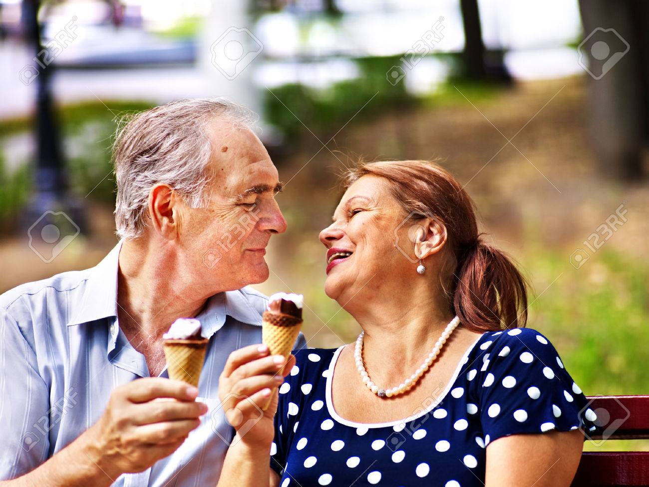 Happy old couple eating ice-cream outdoor. - 28373746