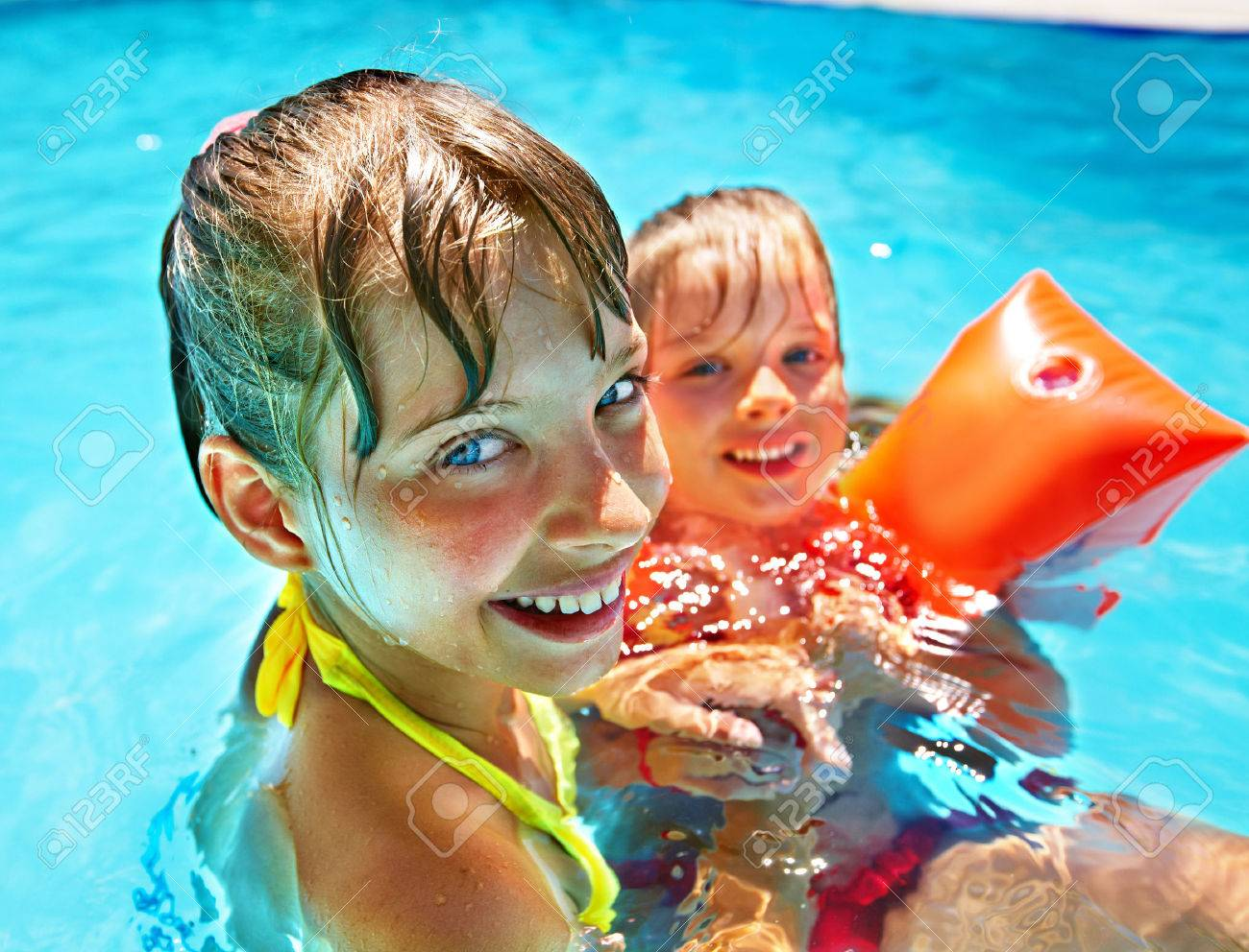 Children with armbands in swimming pool. - 28393739