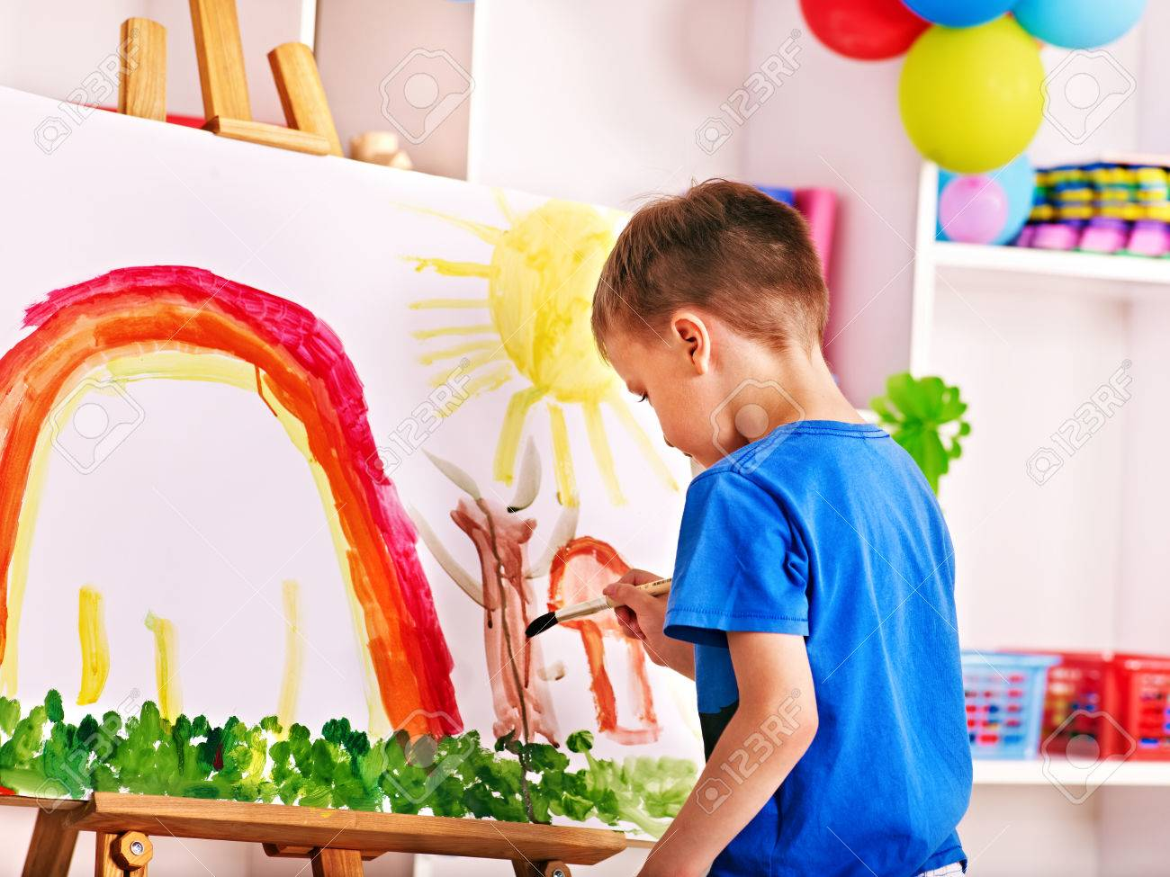 Child painting at easel in school. Education. - 28393911