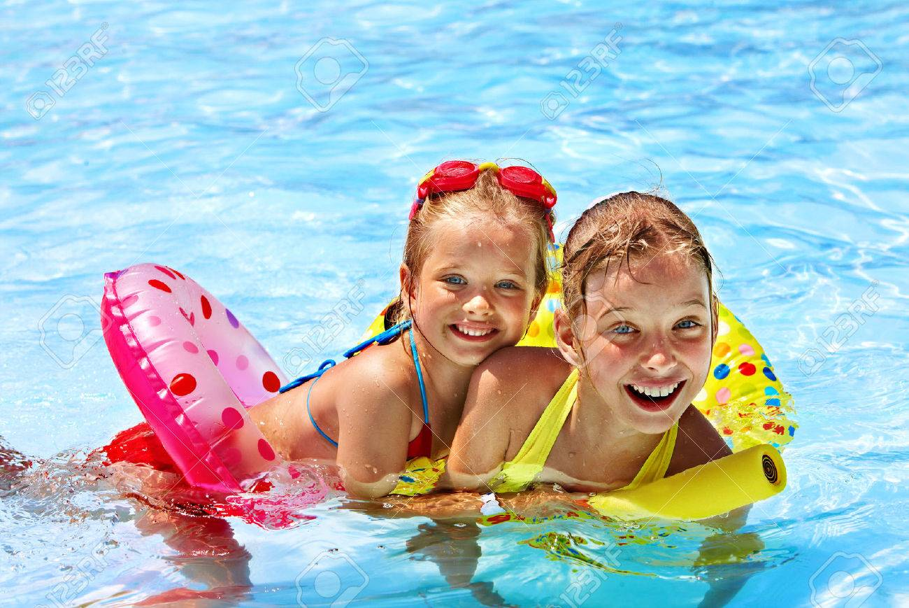 Children sitting on inflatable ring in swimming pool. - 28786899