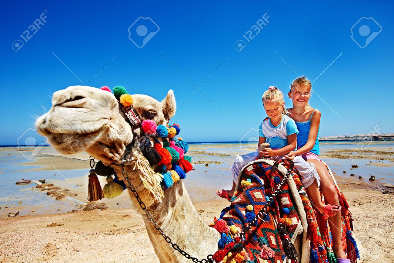 Tourists children riding camel on the beach of Egypt. Sharpness on a camel. - 29177833