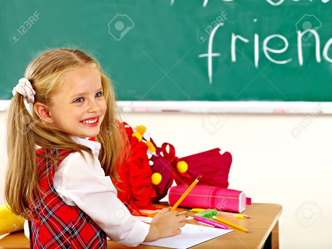 Child holding school cone in classroom. - 30839440