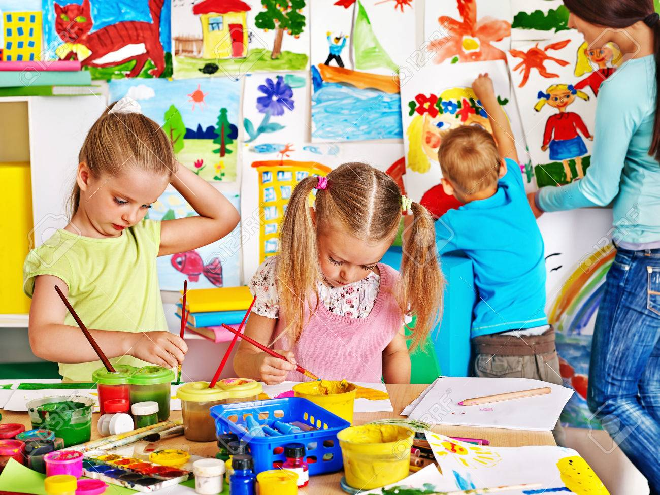 Happy children with teacher painting. - 30839467
