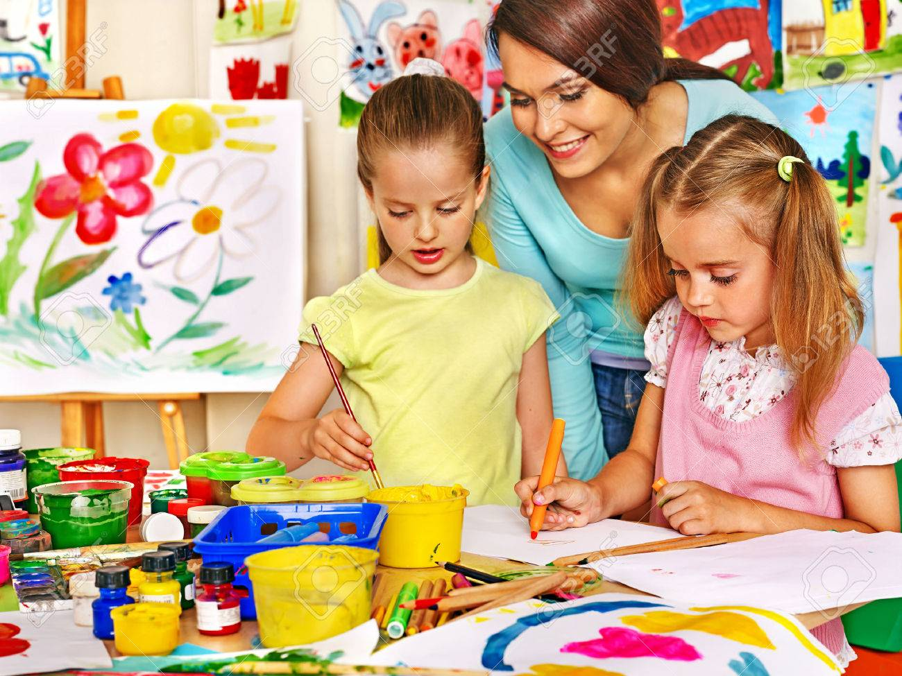 Happy children with teacher painting. - 31450374