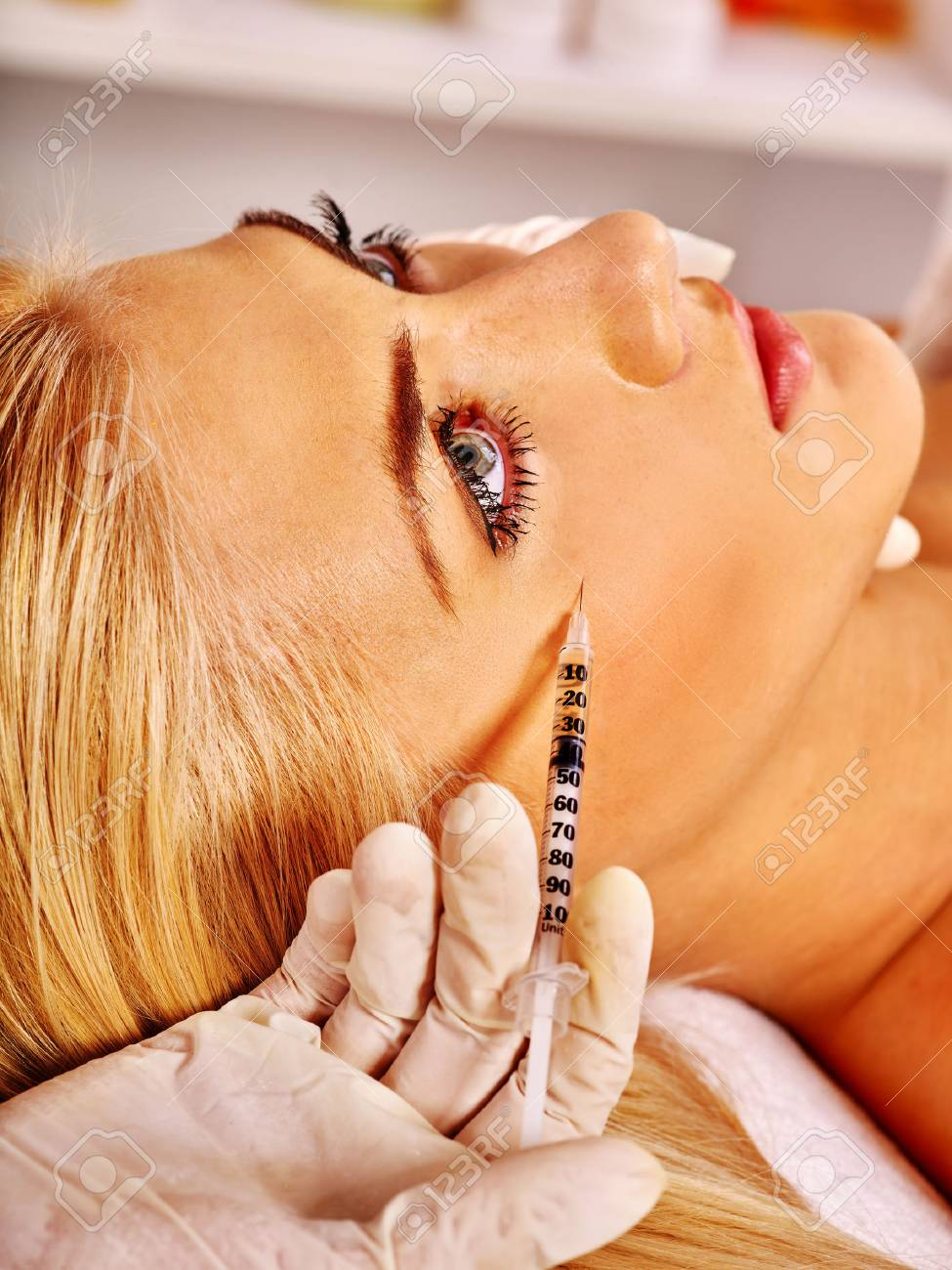 Doctor woman giving botox injections under eye