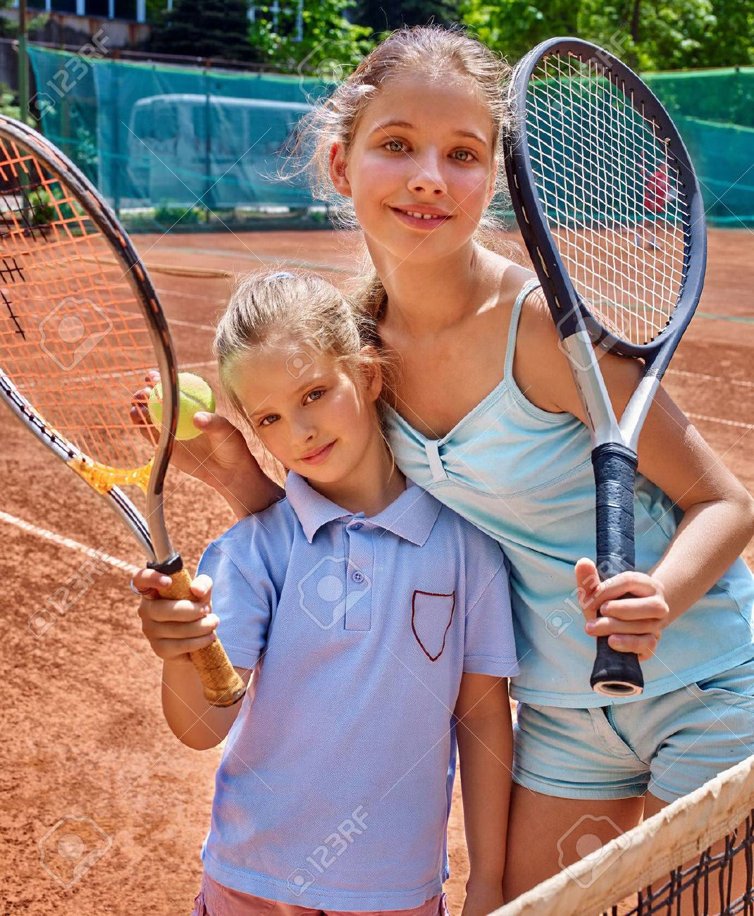 Two sport kids girl with racket and ball on brown tennis court. - 40457152
