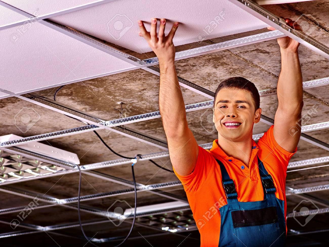 Man in builder uniform hand up installing suspended ceiling - 42492841