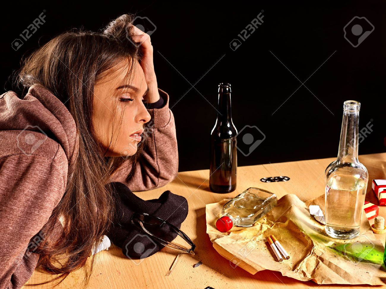 Girl in depression drinking alcohol and smokes cigarettes in solitude at the table. - 46947924