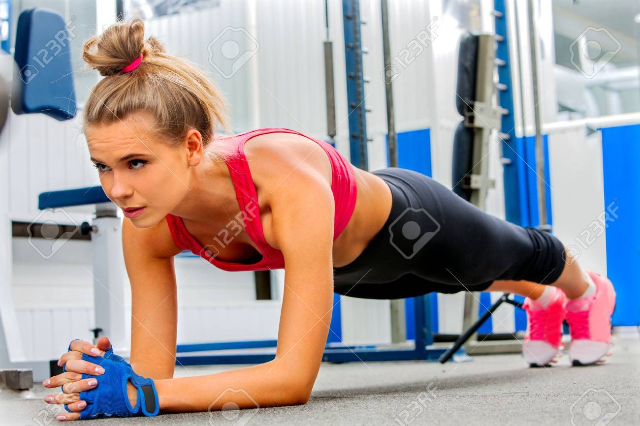 Young woman doing some push ups in gym. Stock Photo - 47314014