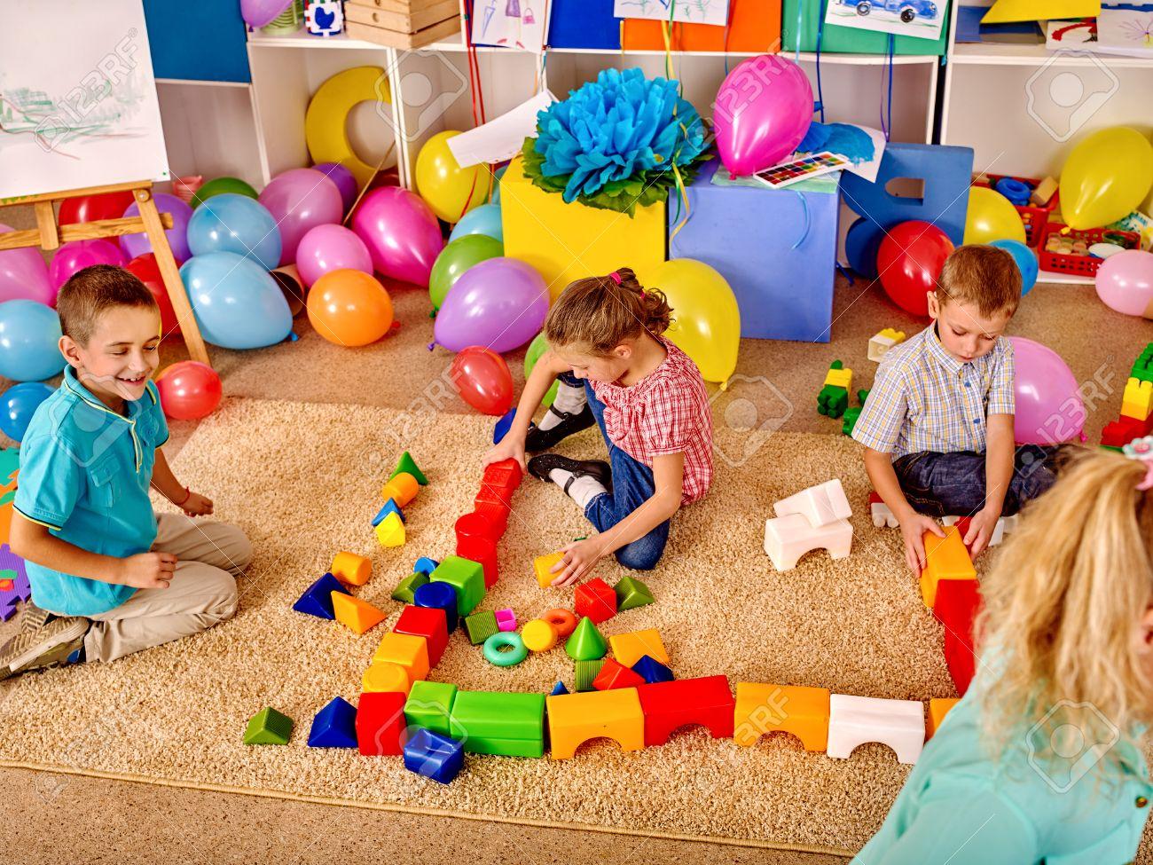 Group children game blocks on carpet floor in kindergarten . Top view. - 47420152