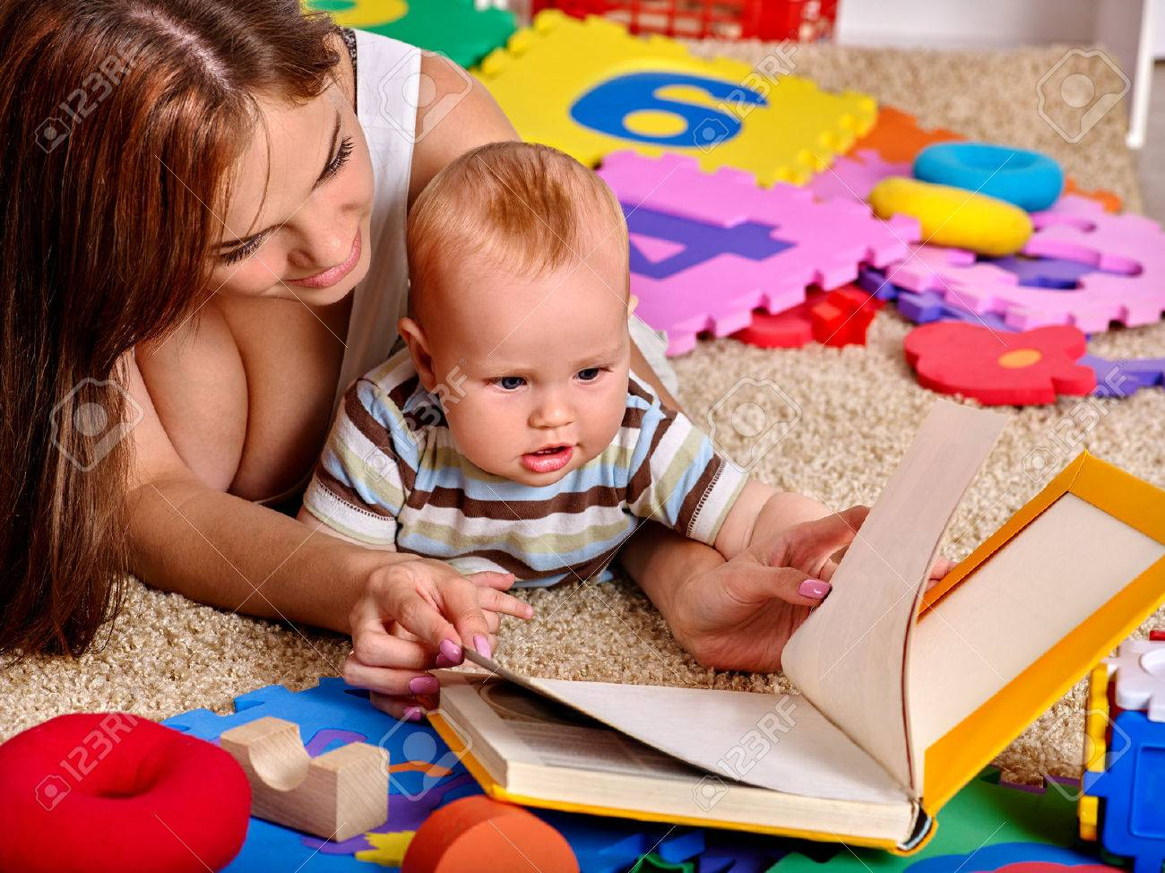 Kid baby boy with mother lying on floor and reading book at home. - 47702473