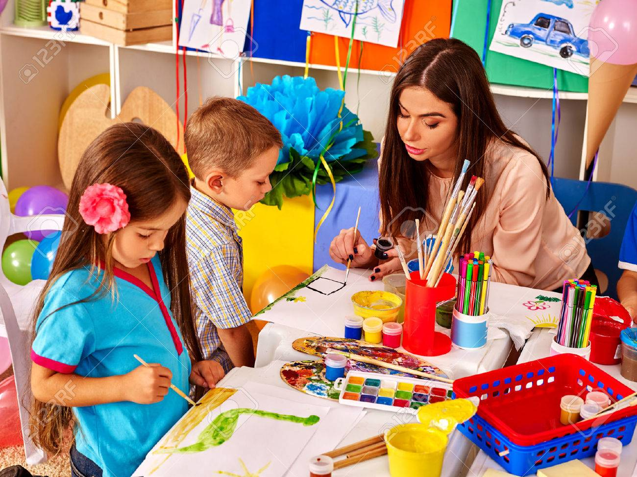 children with teacher woman painting on paper at table in kindergarten group people stock - Children Painting Pictures