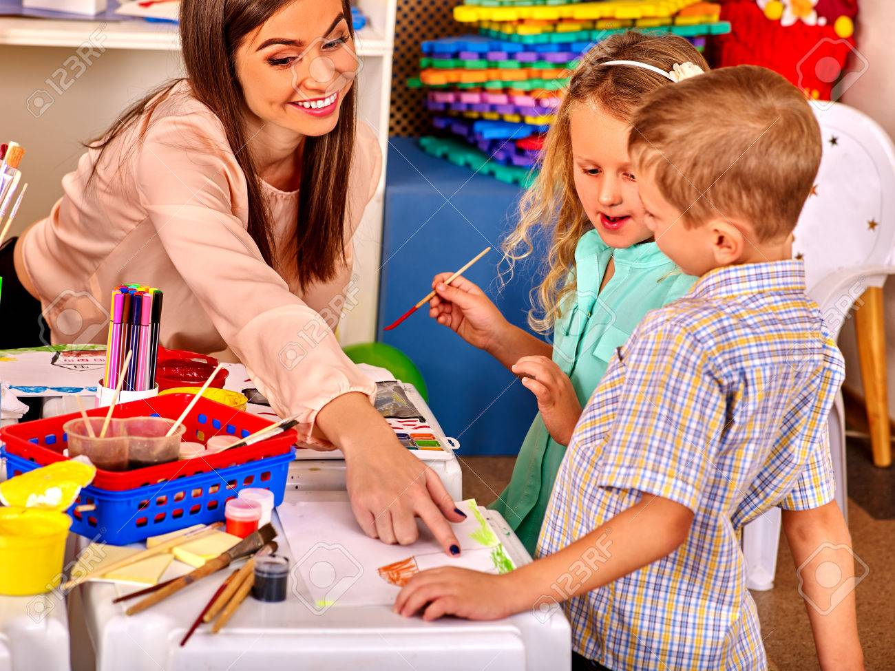 Children small group with teacher woman painting on paper at table in kindergarten . - 48472539