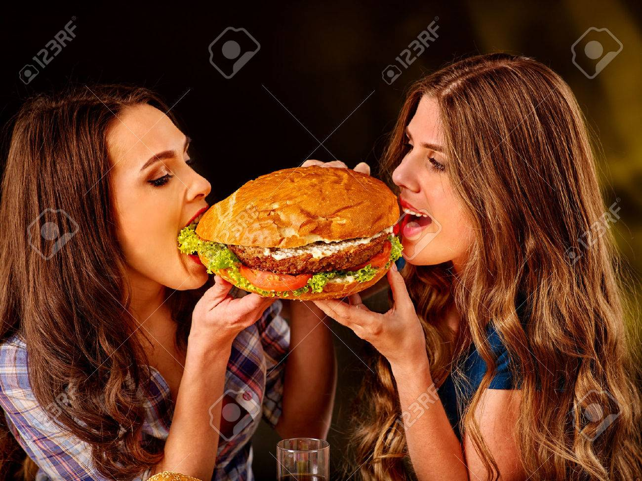 Girl holding and bite big hamburger from different sides. Fastfood concept. Cheeseburger on foreground. - 48930228