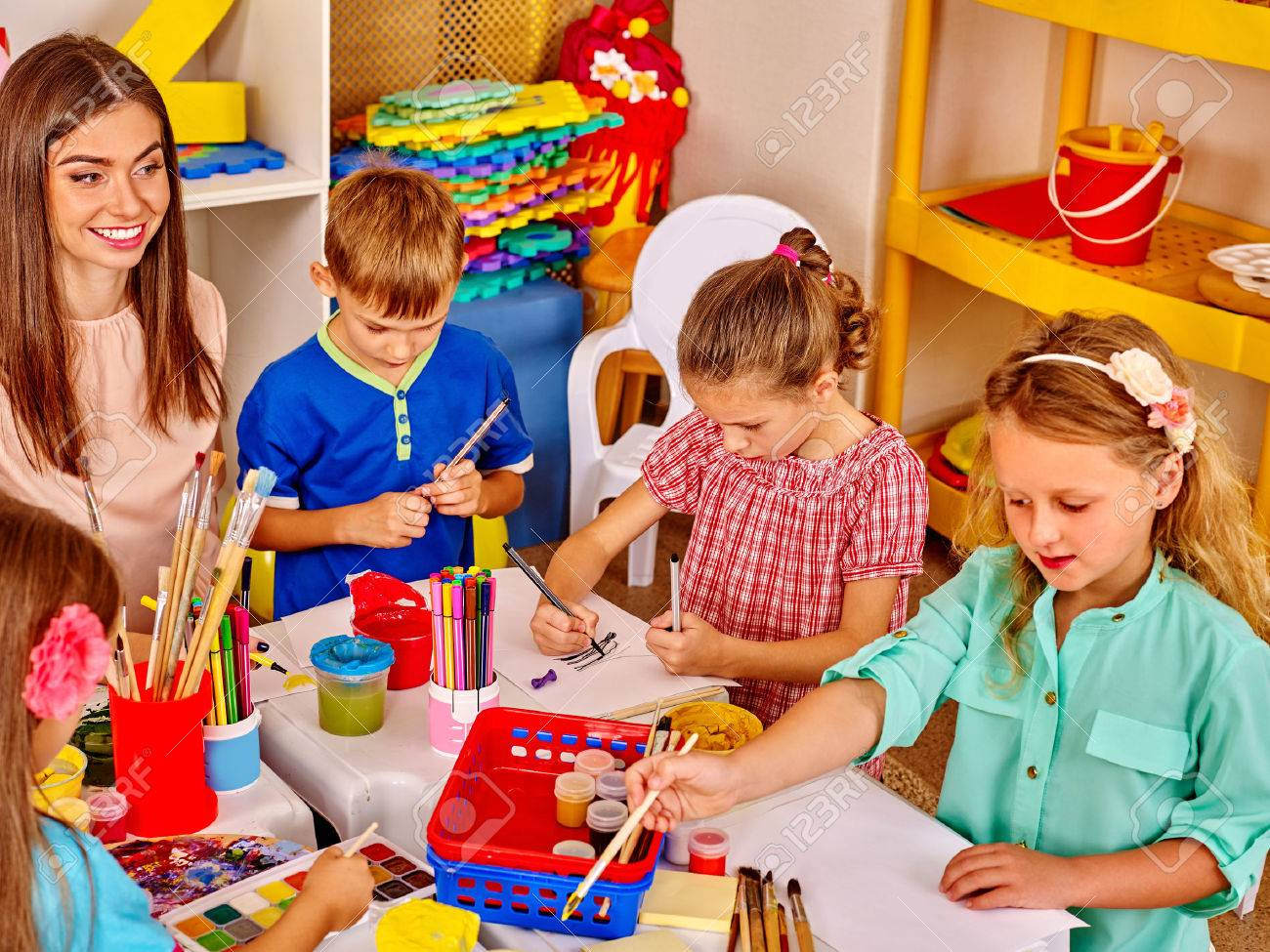 Group kids with teacher woman learnig painting on paper in kindergarten . - 50990411