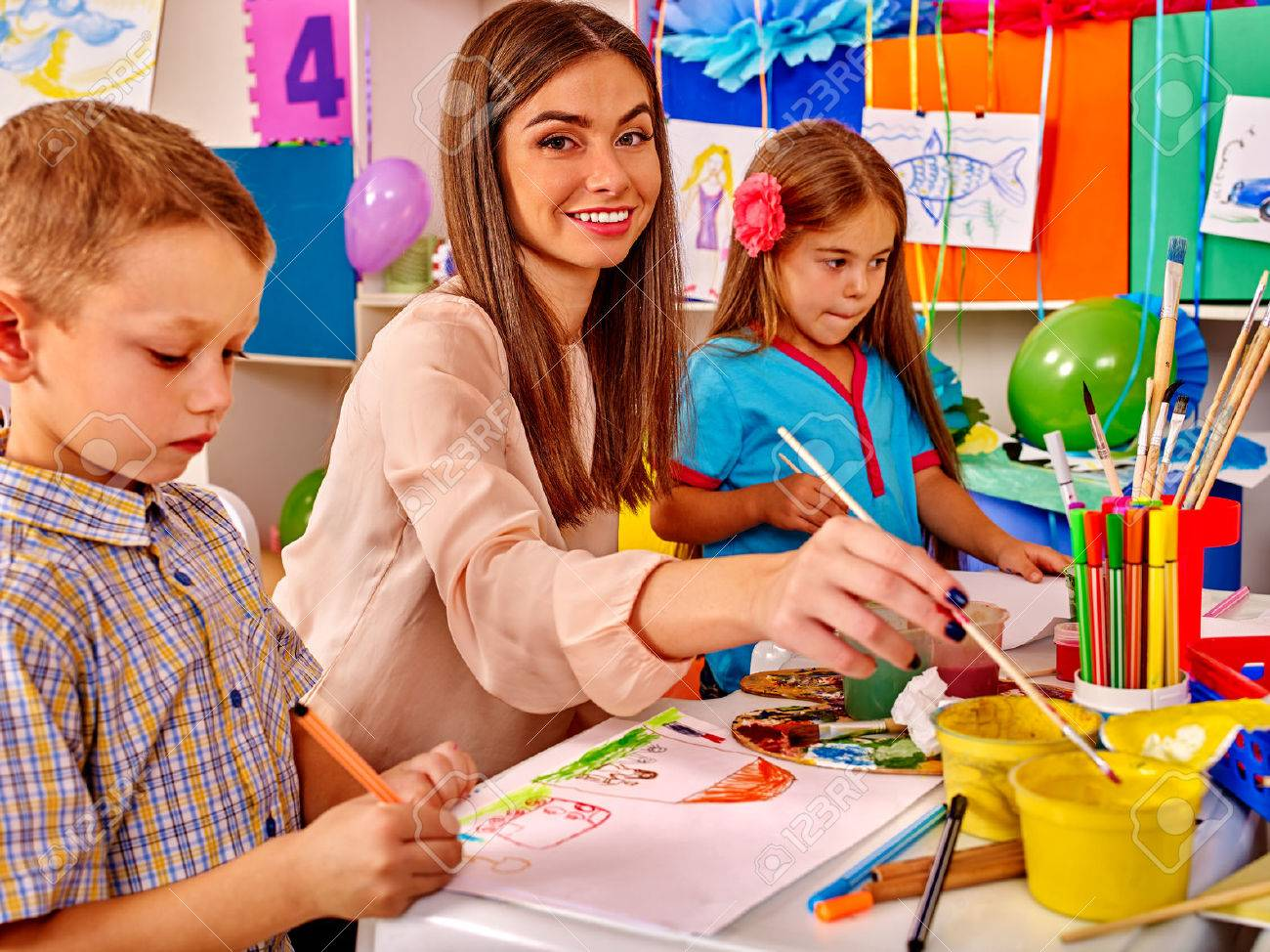 Children with female teacher painting on paper by paint and pencils in kindergarten . - 51120484