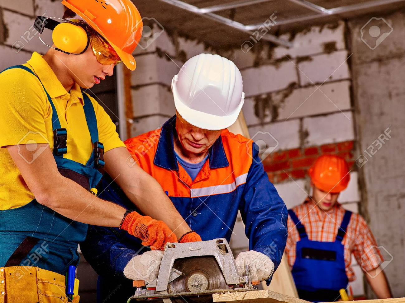 Working group people builder with circular saw. Brick wall in background. - 51599481