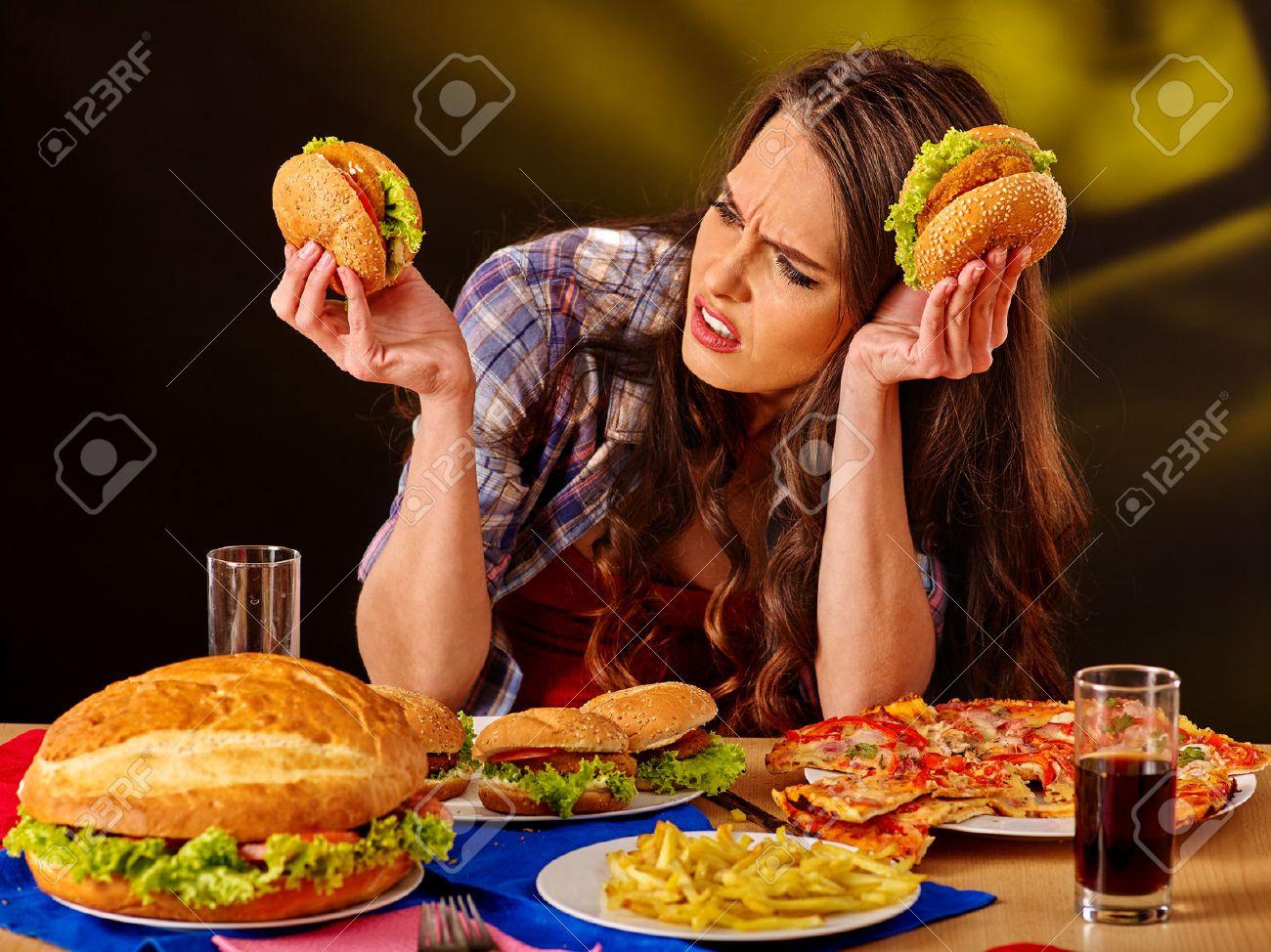 Unhappy girl eat cheap fastfood big hamburger and pizza . - 52232357