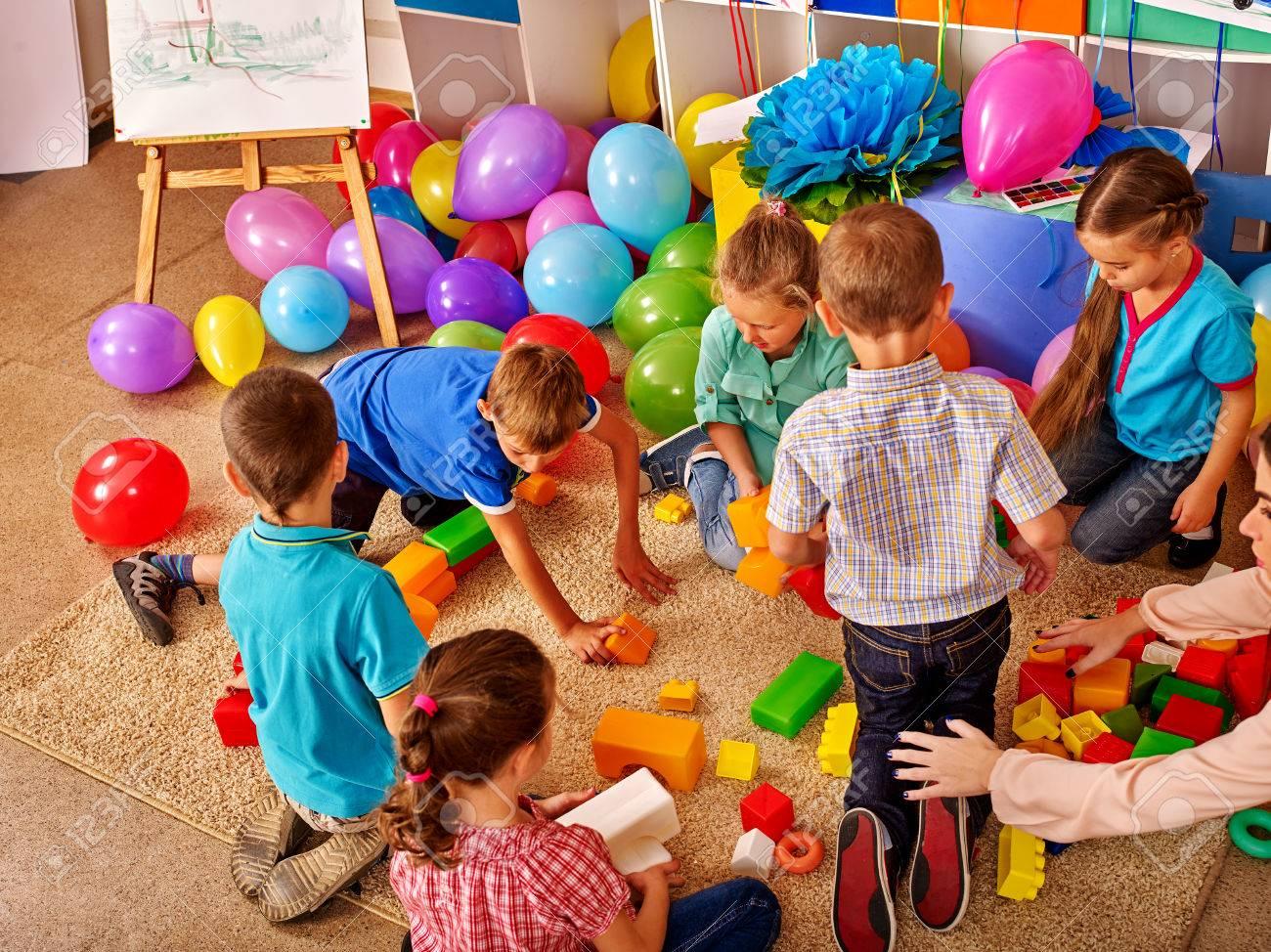 Group children game blocks on floor in kindergarten . Balloons on floor Top view. - 54726546