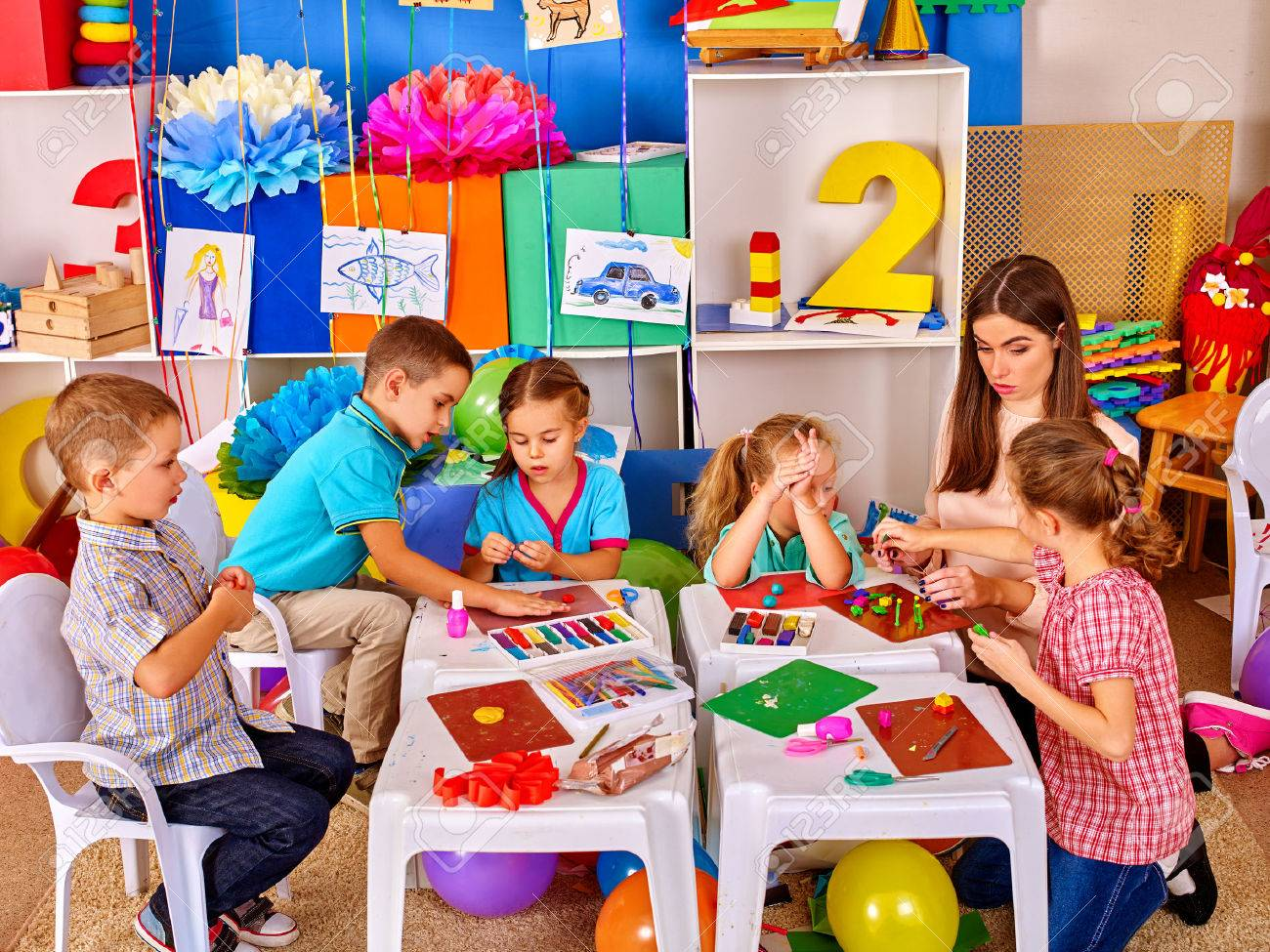 Group clever children with young beautiful teacher mold from plasticine in primary school. Children school education. - 61556738