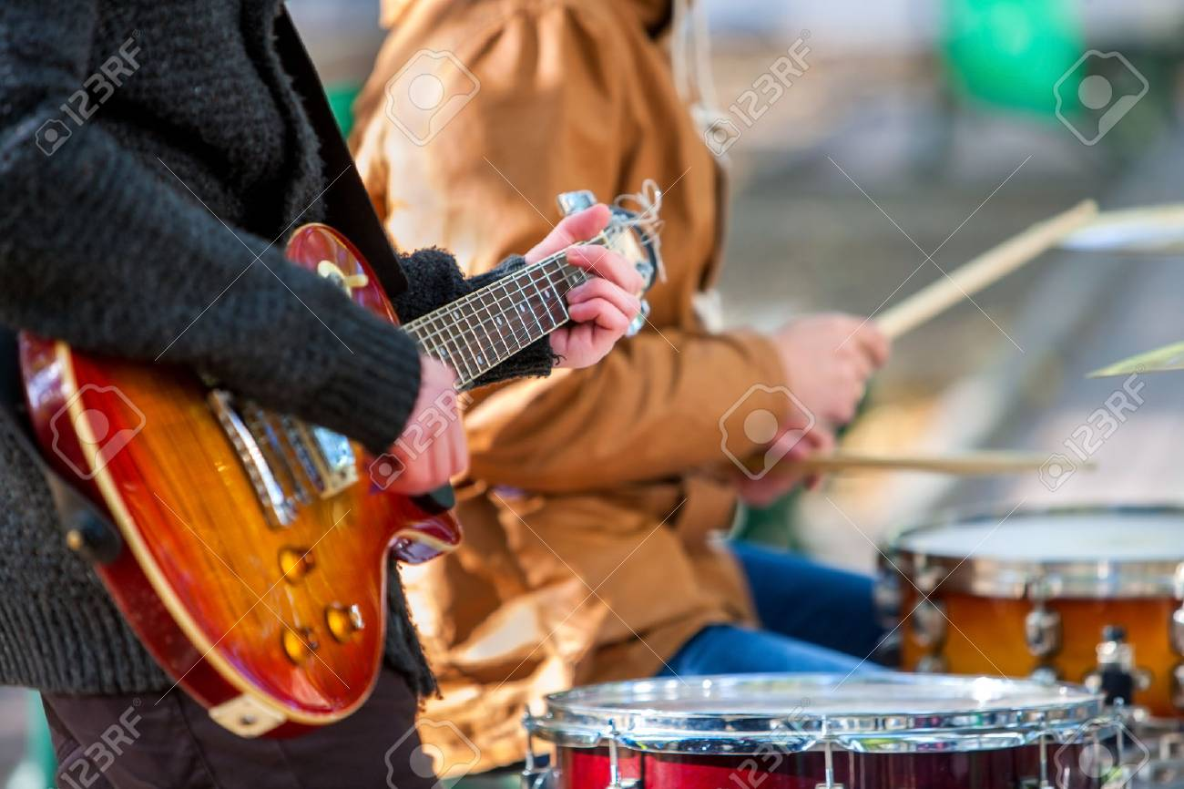 Music street performers on autumn outdoor. Middle section of body part with guitar. - 63136328