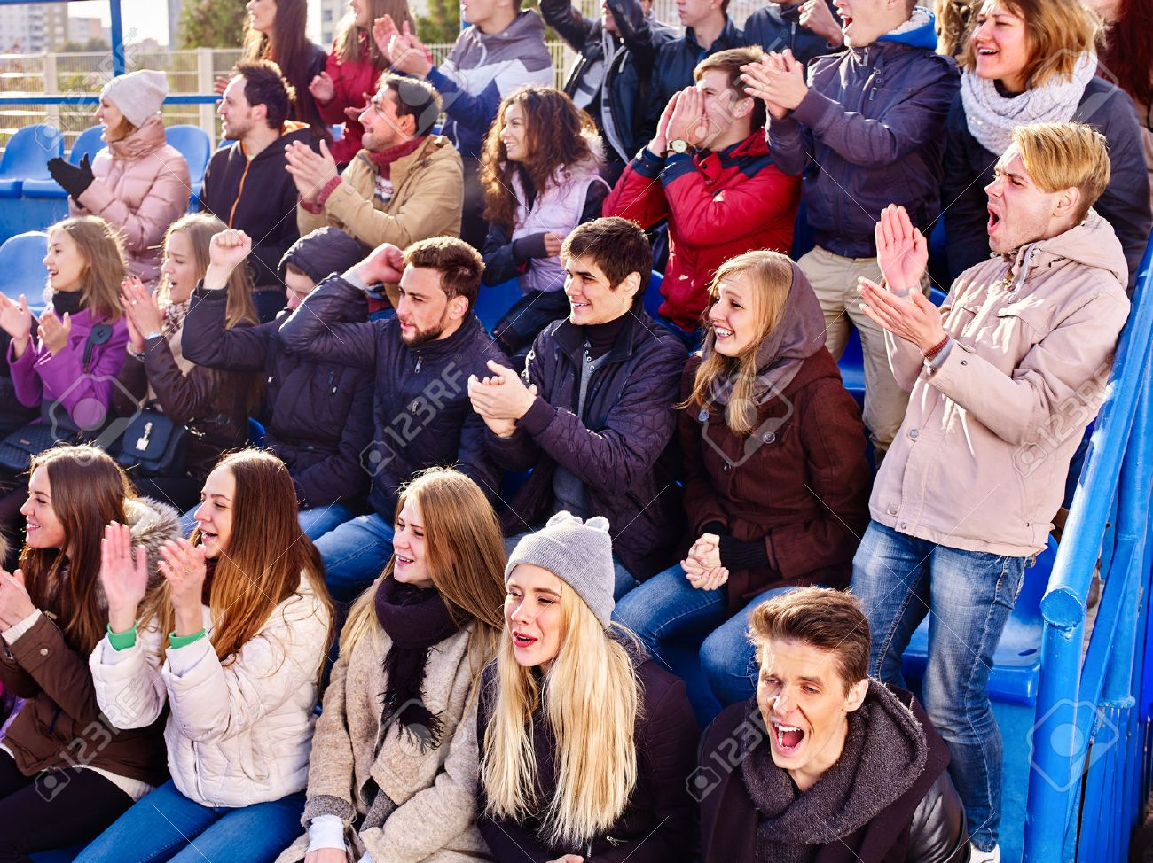 Fans cheering in stadium people applaud your favorite team and singing on tribunes. Group youth group support your favorite team. - 70689881