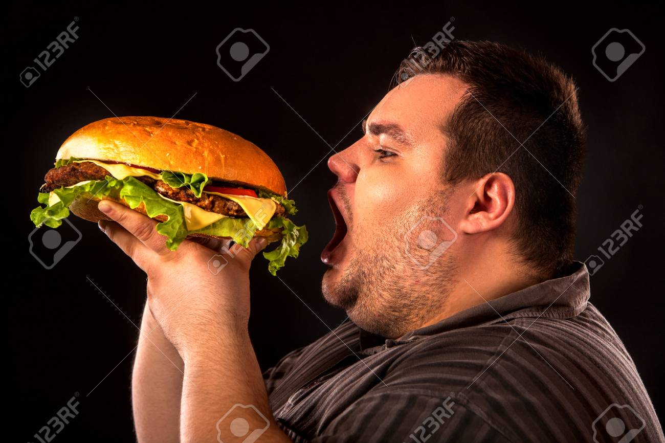 Diet failure of fat man eating fast food hamberger. Breakfast for overweight person who spoiled healthy food by eating huge hamburger. Junk meal leads to obesity. Person regularly overeats concept . - 76186175