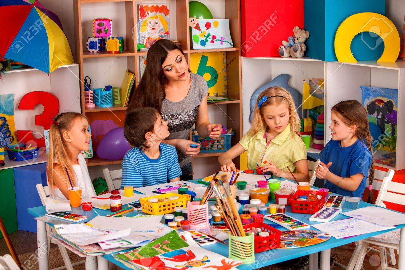 Small Students With Teacher Finger Painting In Art School Class