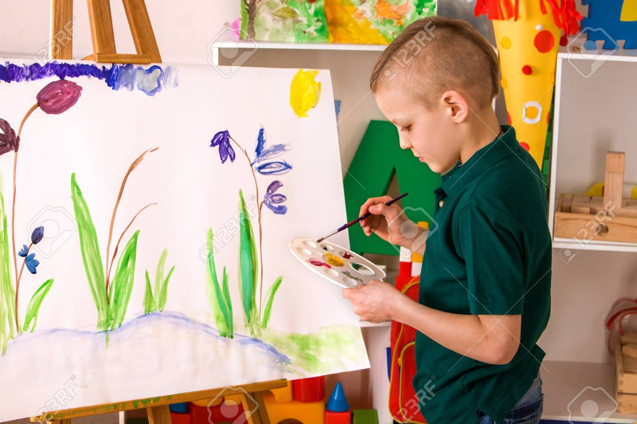 Child painting on easel kid boy learn paint by brush in class school kindergarten