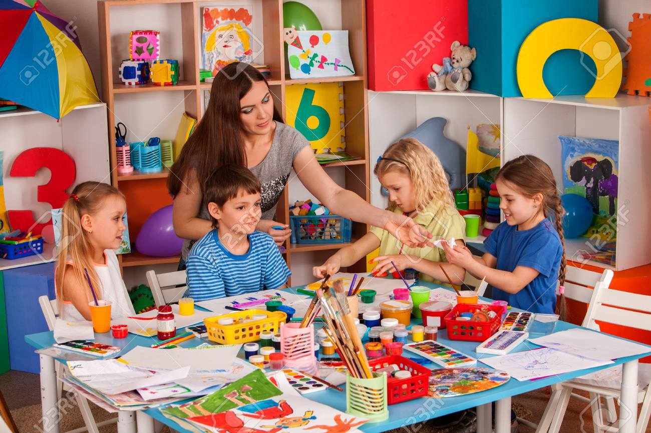 Kids playroom organization of children painting and drawing in kids club. Craft lesson in primary school. Teaching children to do common project. - 95220266