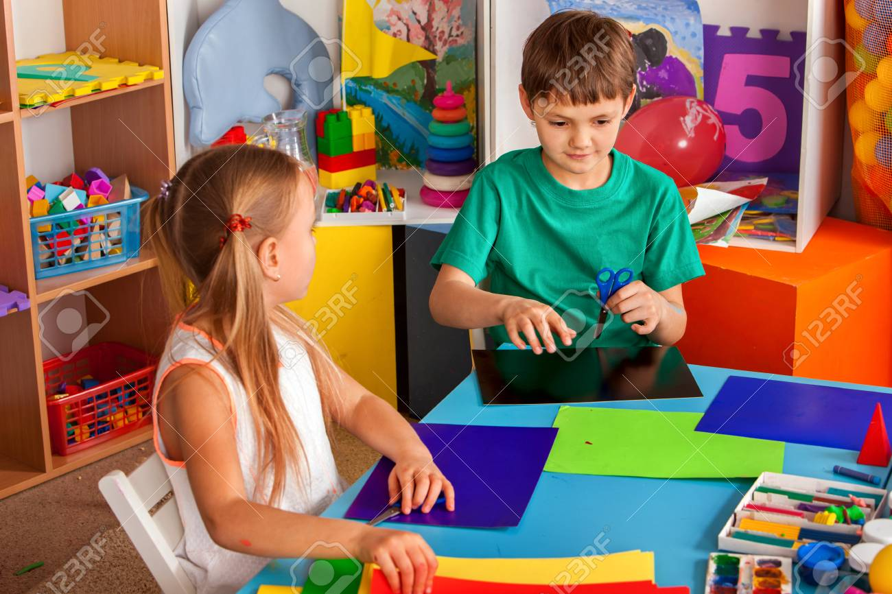 School children with scissors in kids hands cutting paper with teacher in class room. Childrens project in kindergarten. Large group girls and boys together. Origami exhibition. - 98178297