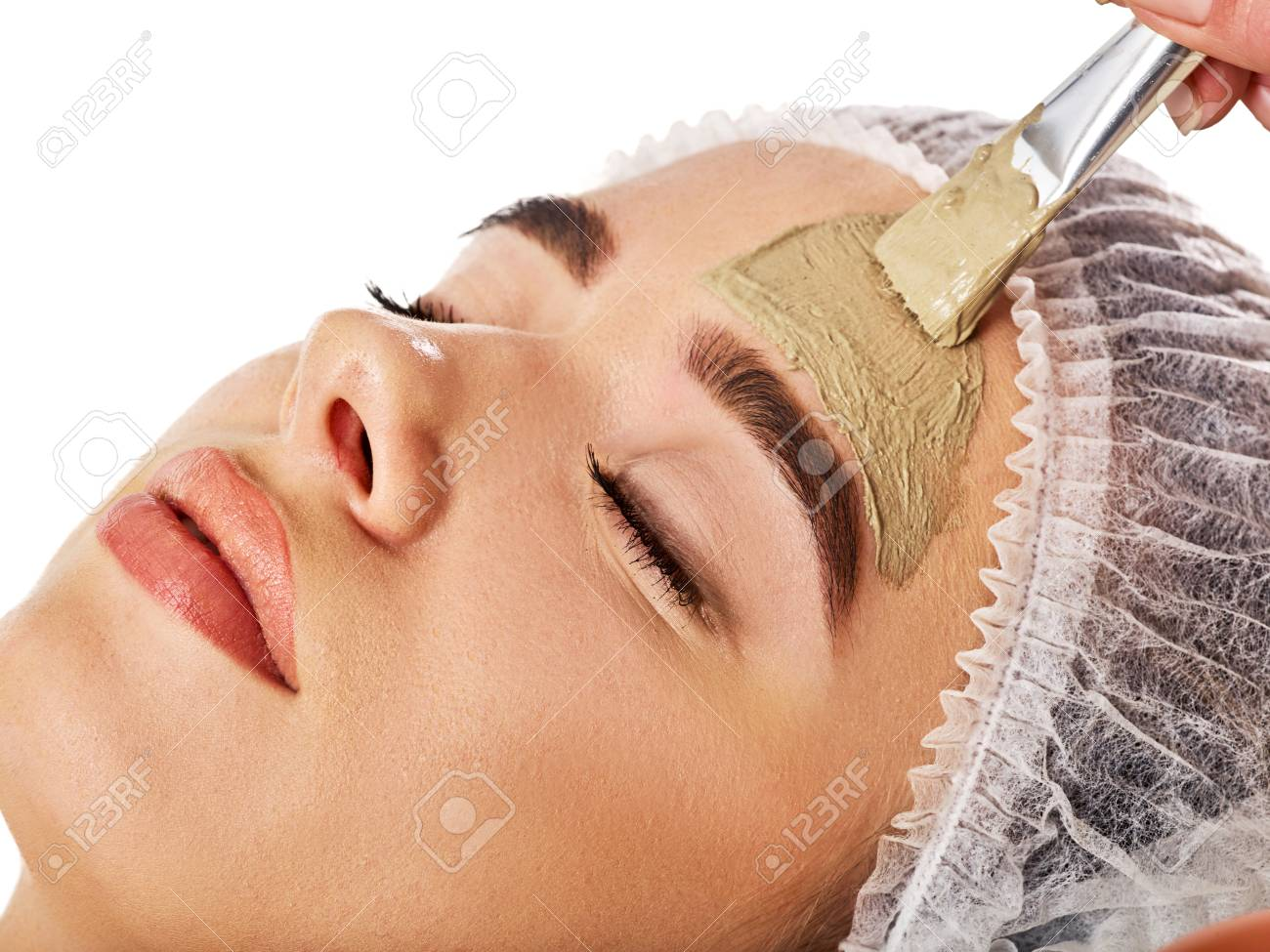 Mud facial mask of woman in spa salon. Massage with clay full face. Girl on with therapy room. Beautician with brush therapeutic procedure isolated background. Healing clay for face. Facelift. - 102254003