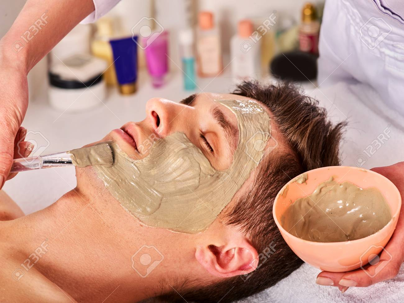 Mud facial mask of man in spa salon. Cleansing massage with clay full face. Lying man on therapy room for skin detox. Beautician with bowl therapeutic procedure. Anti-aging cosmetic mask. - 110289391