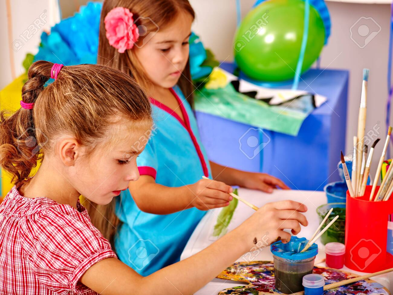 Girls keep brush painting on table in kindergarten . Painting learning. - 122228780