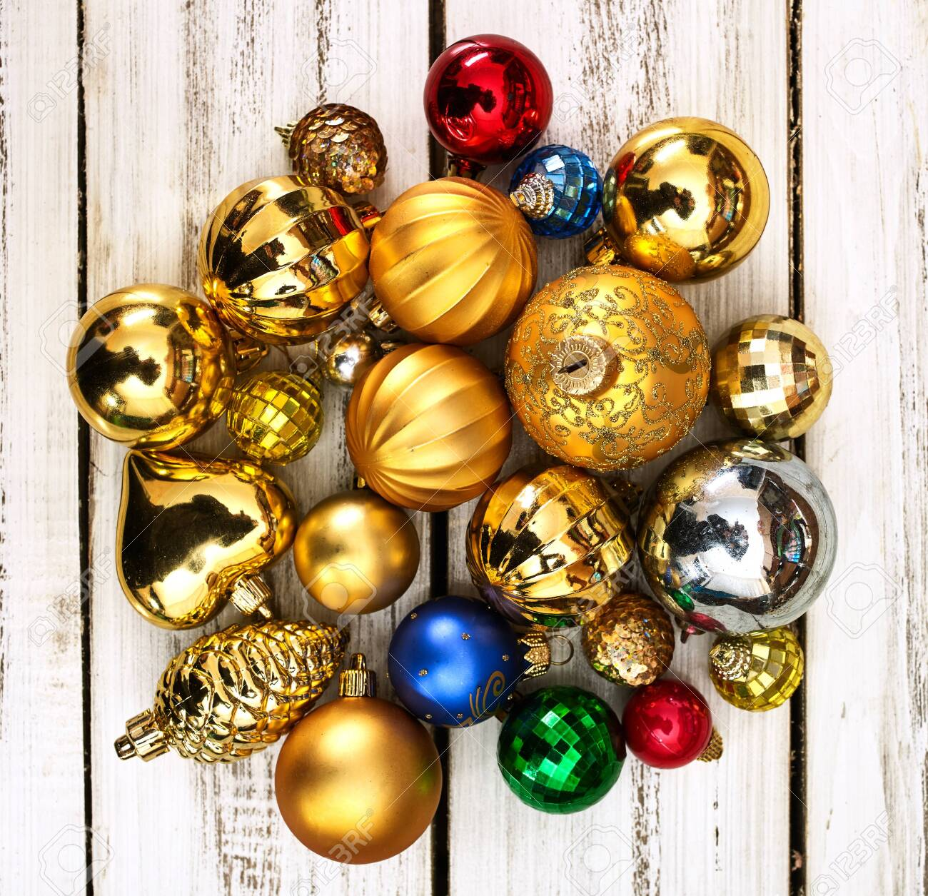 Christmas wreath of Xmas balls decorations hangs on front door who made from white wooden boards on square frame. - 133939728