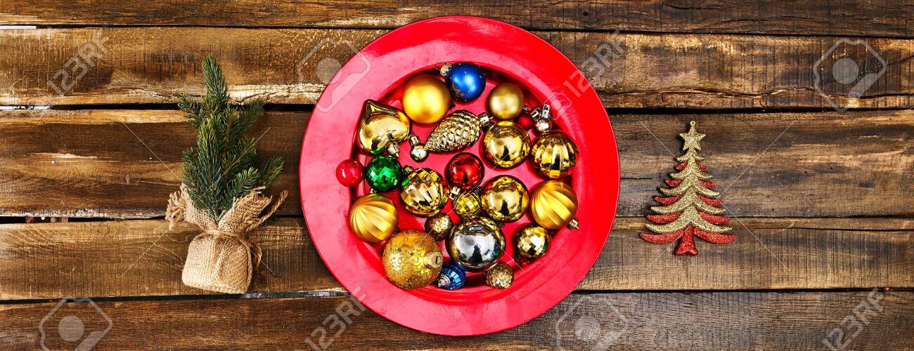 Christmas decorations design of Xmas balls ornaments on red plate with green tree on wooden boards. Horizontal long frame banner. - 133939739