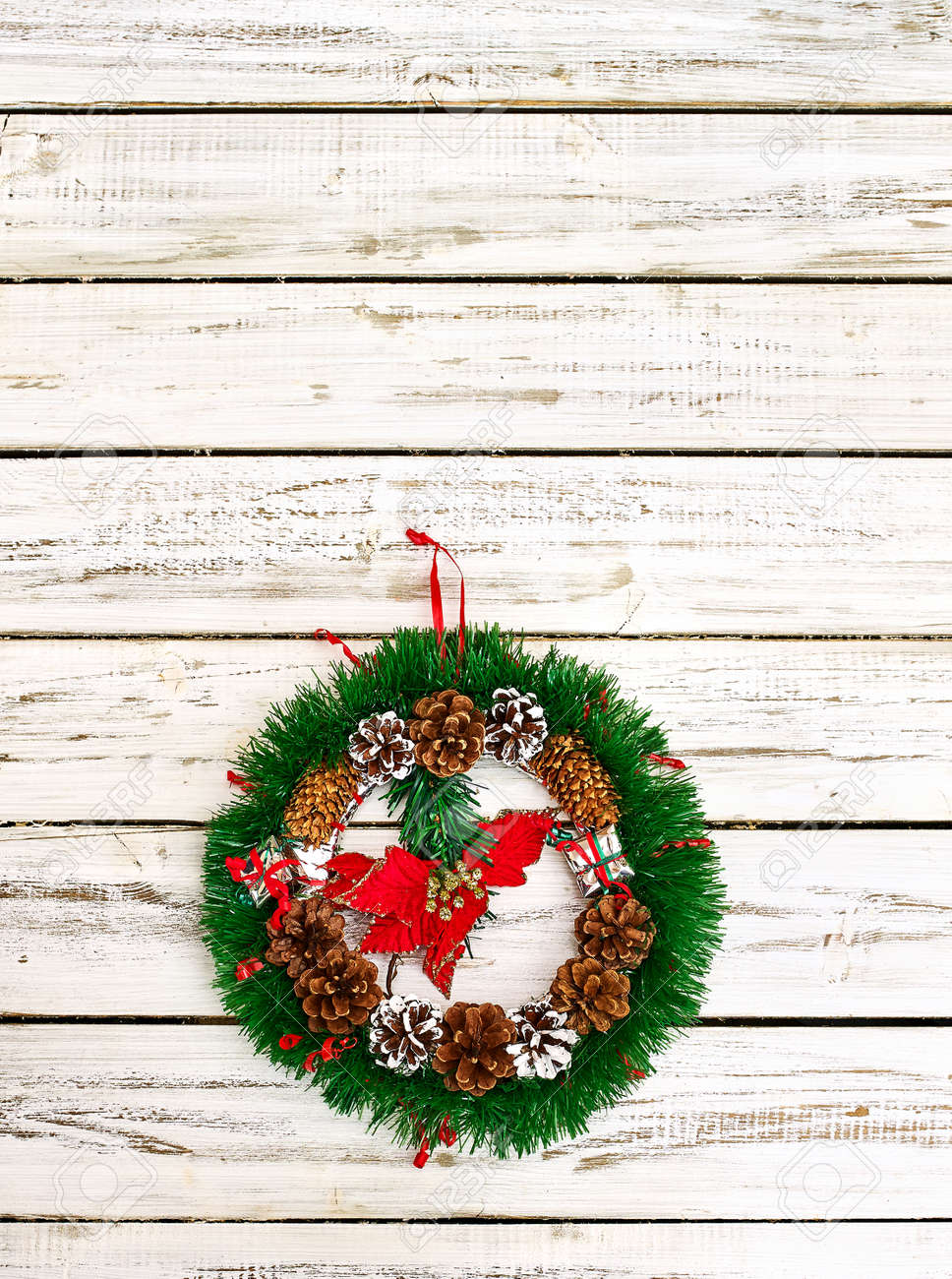 Christmas wreath with winter red flower in middle decoration hangs on white front door. Vertical frame with copy space top. - 133940076