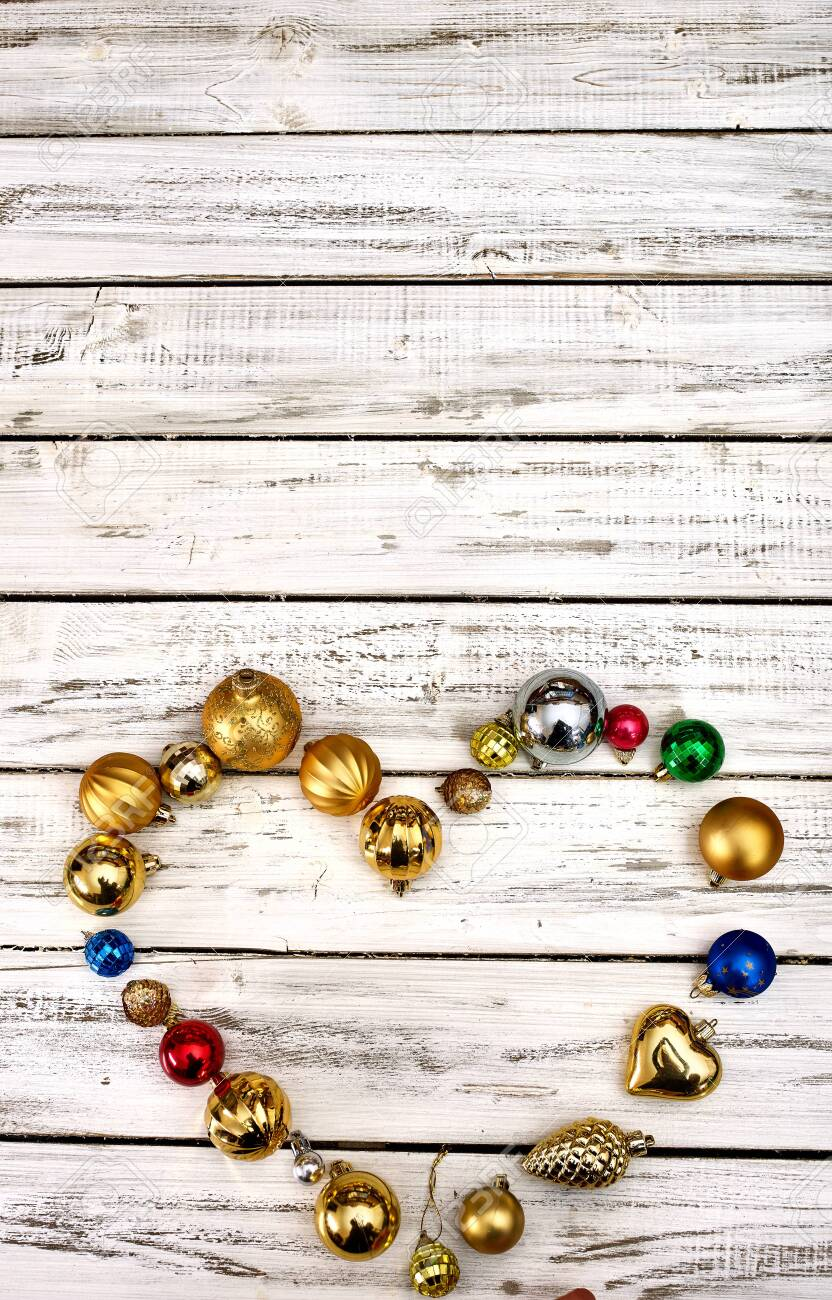 Christmas decorations scattered heart form design top view of Xmas balls ornaments on white wooden table. Vertical long frame with copy space up frame. - 133940068