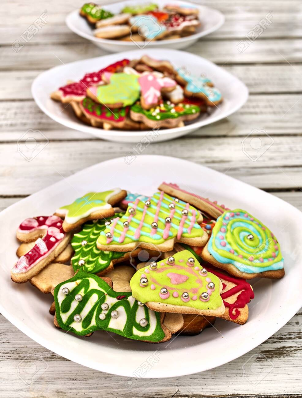 Christmas gingerbread cookies on three plates by white wooden table . Top view long vertical design frame. - 133940075