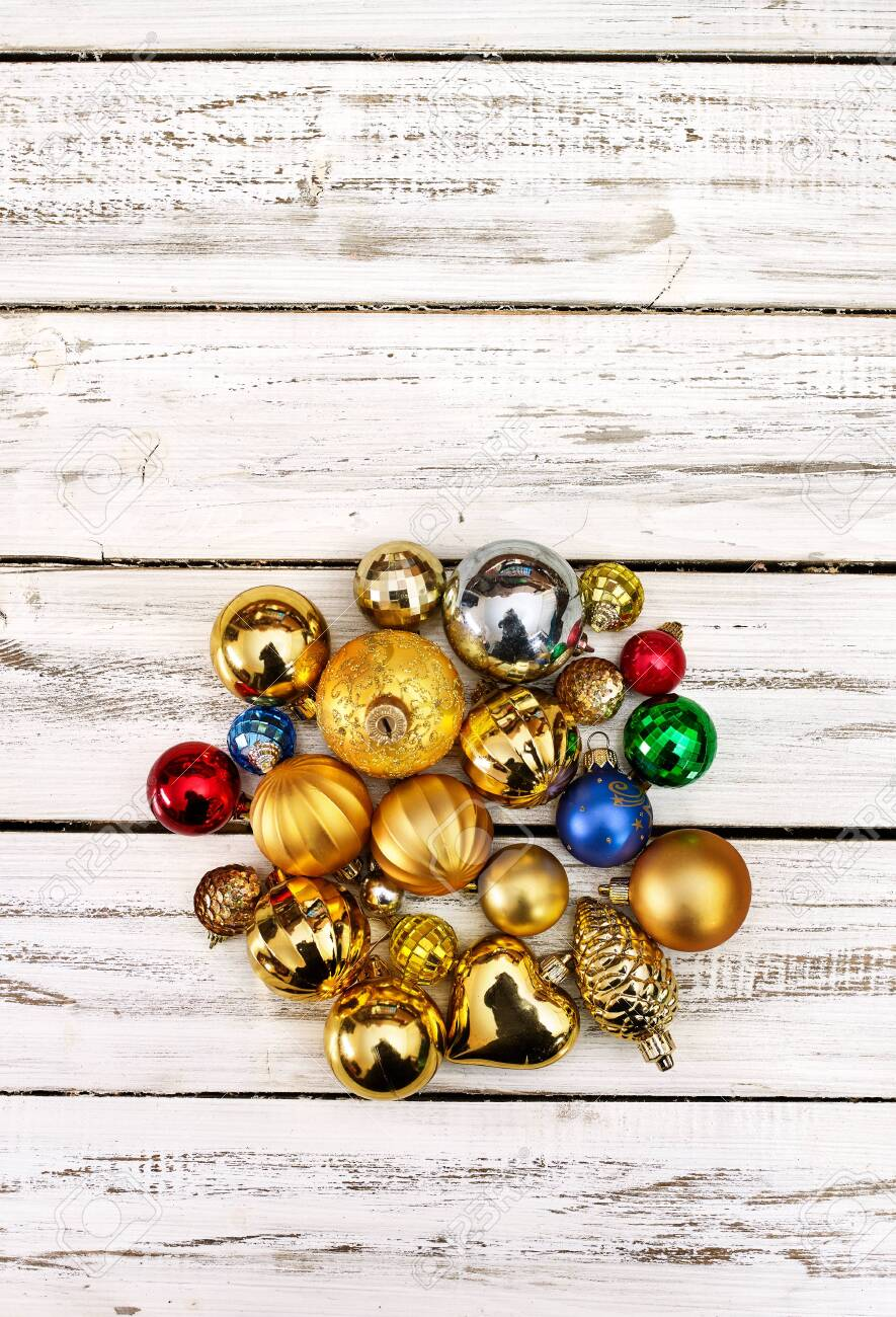 Christmas stack of Xmas balls decorations on white wooden boards on vertical long frame with copy space up frame. - 133940081